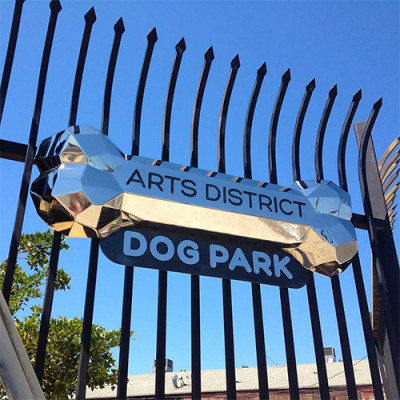 Fence at the Arts District Dog Park with chrome dog park signage.